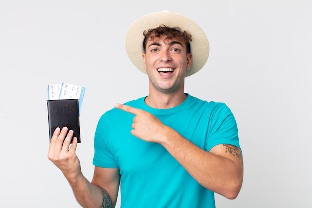 Jonge knappe man die opgewonden en verrast kijkt en naar de zijkant wijst. reiziger met zijn paspoort
