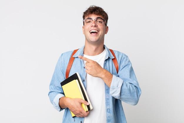 Jonge knappe man die opgewonden en verrast kijkt en naar de zijkant wijst. universitair studentenconcept