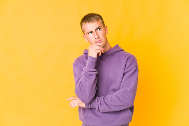 Jonge knappe man die opzij kijkt met een twijfelachtige en sceptische uitdrukking