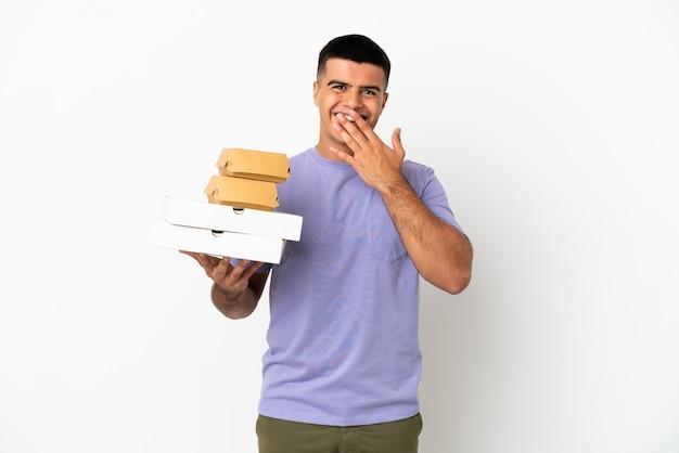 Jonge knappe man die pizza's en hamburgers vasthoudt over een geïsoleerde witte achtergrond, blij en glimlachend die mond bedekt met hand