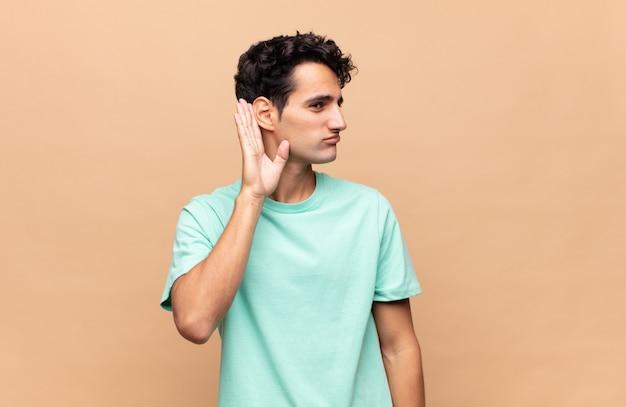 Jonge knappe man die serieus en nieuwsgierig kijkt, luistert, probeert een geheim gesprek of roddel te horen, afluisteren