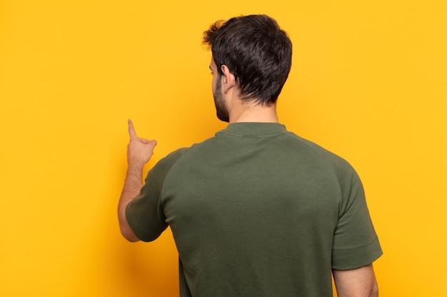 Jonge knappe man die staat en wijst naar object op kopieerruimte, achteraanzicht