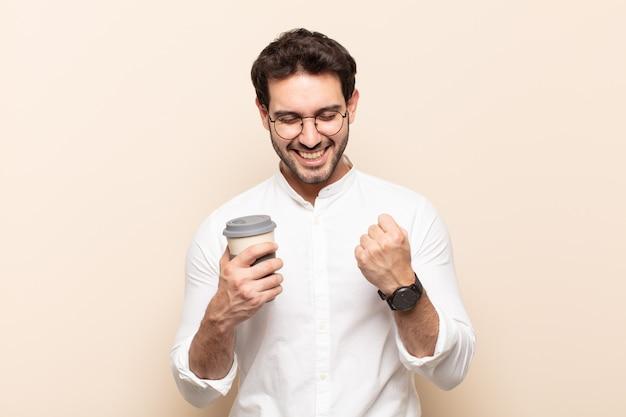 Jonge knappe man die triomfantelijk schreeuwt, lacht en zich blij en opgewonden voelt terwijl hij succes viert
