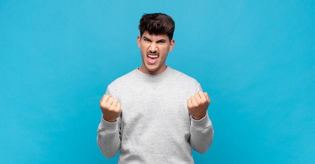 Jonge knappe man die triomfantelijk schreeuwt, lacht en zich gelukkig voelt