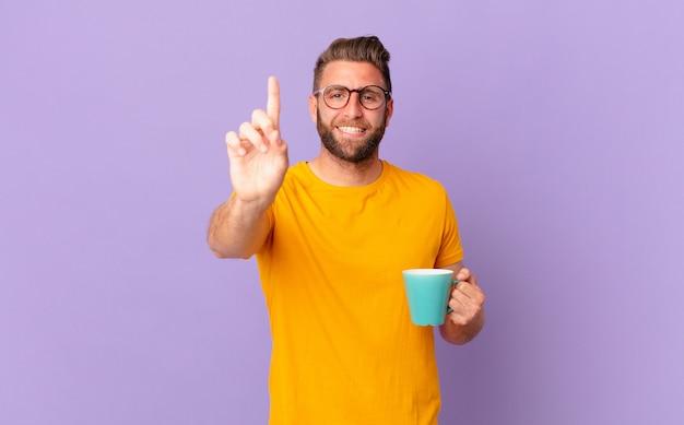 Jonge knappe man die trots en zelfverzekerd glimlacht en nummer één maakt. en een koffiemok vasthouden