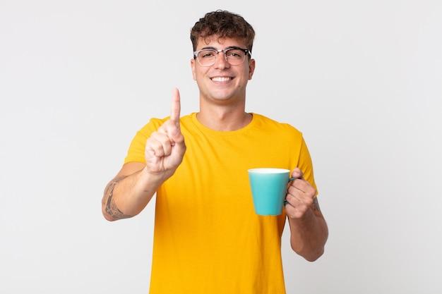 Jonge knappe man die trots en zelfverzekerd glimlacht en nummer één maakt en een kopje koffie vasthoudt