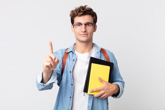 Jonge knappe man die trots en zelfverzekerd glimlacht en nummer één maakt. universitair studentenconcept