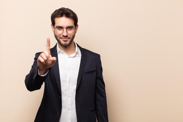Jonge knappe man die trots en zelfverzekerd glimlacht en nummer één triomfantelijk laat poseren, zich als een leider voelt