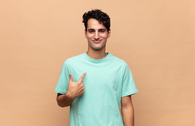 Jonge knappe man die trots, zelfverzekerd en gelukkig kijkt, glimlacht en naar zichzelf wijst of nummer één maakt