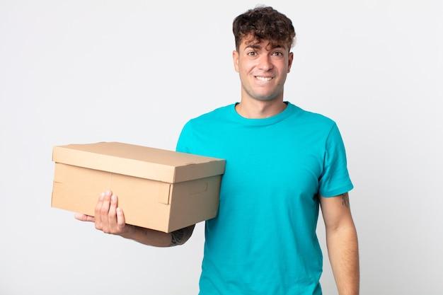 Jonge knappe man die verbaasd en verward kijkt en een kartonnen doos vasthoudt