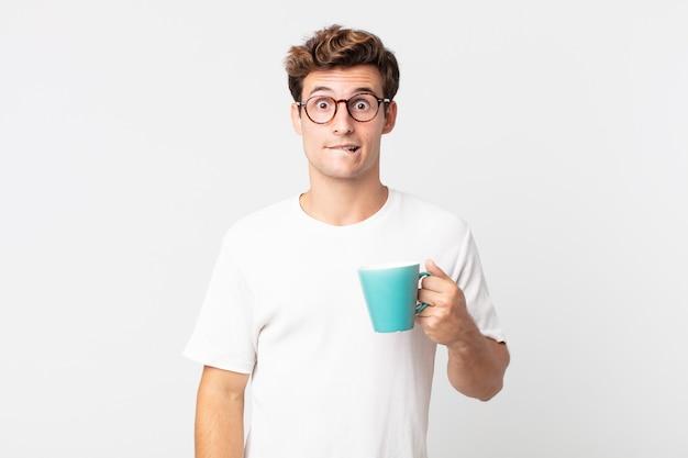 Jonge knappe man die verbaasd en verward kijkt en een koffiekopje vasthoudt