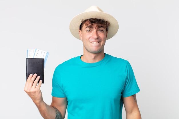 Jonge knappe man die verbaasd en verward kijkt. reiziger met zijn paspoort