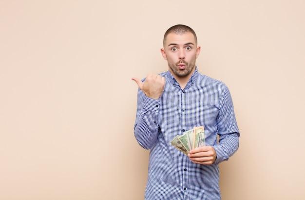 Jonge knappe man die verbaasd in ongeloof kijkt, naar een object aan de zijkant wijst en wauw zegt, ongelooflijk met dollarbankbiljetten