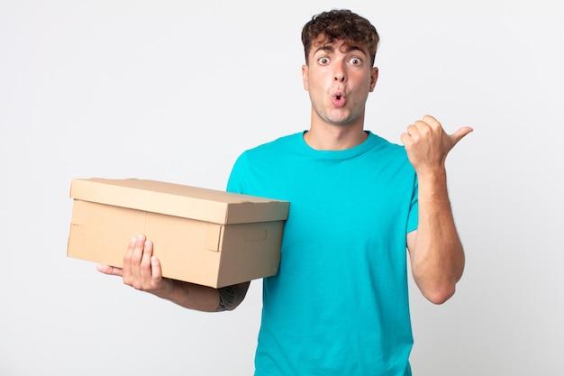 Jonge knappe man die verbaasd kijkt in ongeloof en een kartonnen doos vasthoudt