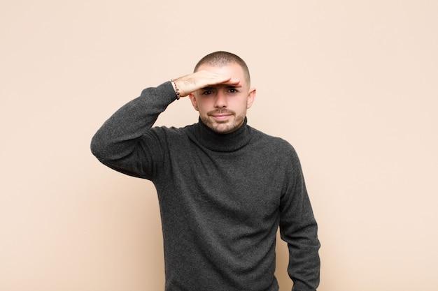 Jonge knappe man die verbijsterd en verbaasd kijkt, met de hand op het voorhoofd ver weg kijkt, kijkt of zoekt op een vlakke muur