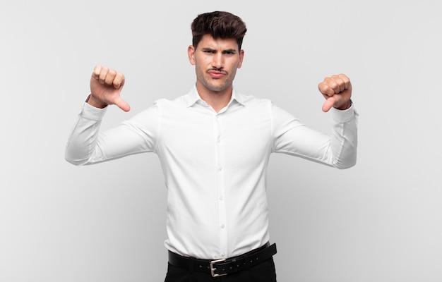 Jonge knappe man die verdrietig, teleurgesteld of boos kijkt, duimen naar beneden toont in onenigheid, zich gefrustreerd voelt
