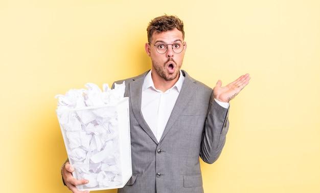 Jonge knappe man die verrast en geschokt kijkt, met open mond die een object met papieren ballen afvalconcept vasthoudt