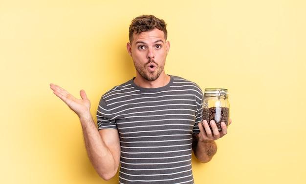 Jonge knappe man die verrast en geschokt kijkt, met open mond terwijl hij een object koffiebonenconcept vasthoudt