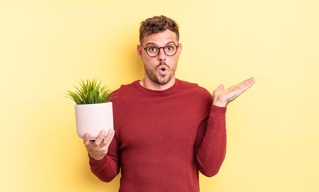 Jonge knappe man die verrast en geschokt kijkt, met open mond terwijl hij een object vasthoudt. decoratief plantenconcept