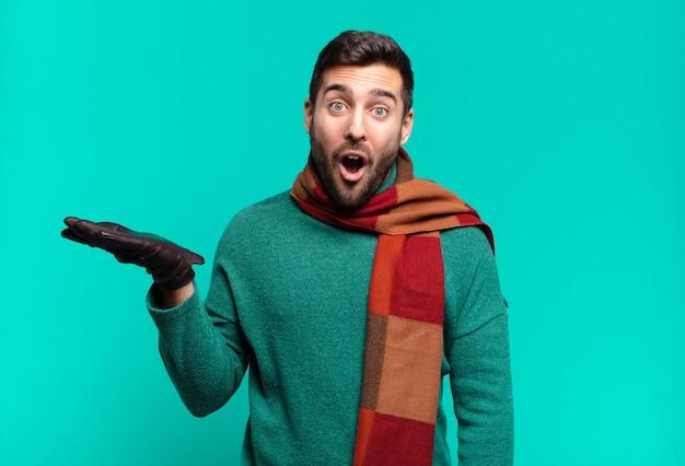 Jonge knappe man die verrast en geschokt kijkt, met open mond terwijl hij een object vasthoudt met een open hand aan de zijkant. koud en winterconcept