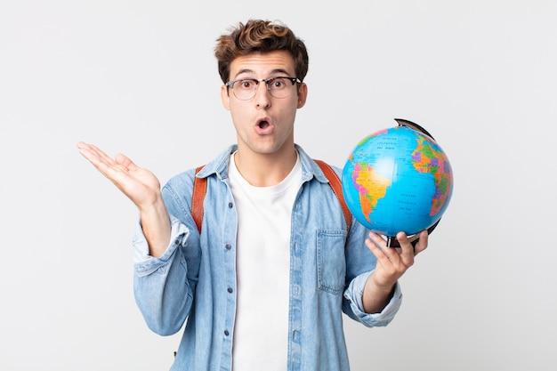 Jonge knappe man die verrast en geschokt kijkt, met open mond terwijl hij een object vasthoudt. student met een wereldbolkaart