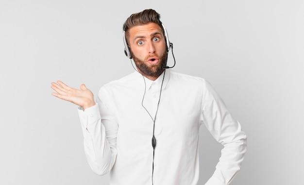 Jonge knappe man die verrast en geschokt kijkt, met open mond terwijl hij een object vasthoudt. telemarketing concept