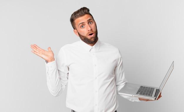 Jonge knappe man die verrast en geschokt kijkt, met open mond terwijl hij een voorwerp vasthoudt en een laptop vasthoudt