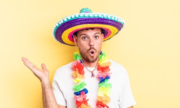 Jonge knappe man die verrast en geschokt kijkt, met open mond terwijl hij een voorwerp vasthoudt. mexicaans feestconcept