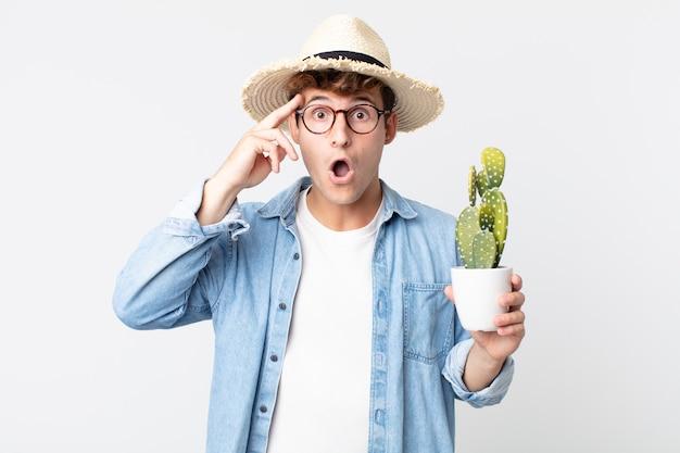 Jonge knappe man die verrast kijkt en een nieuwe gedachte, idee of concept realiseert. boer met een decoratieve cactus