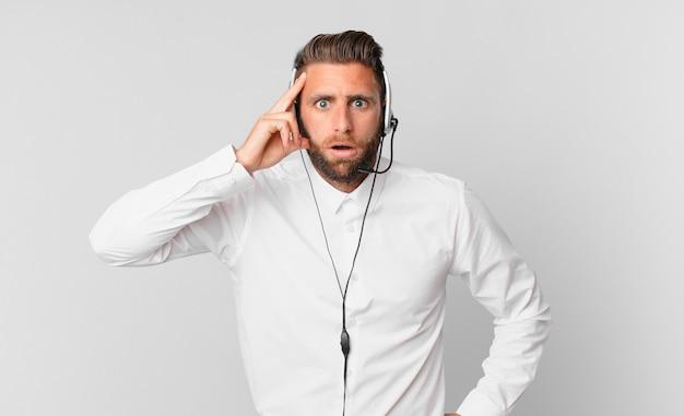 Jonge knappe man die verrast kijkt en een nieuwe gedachte, idee of concept realiseert. telemarketing concept