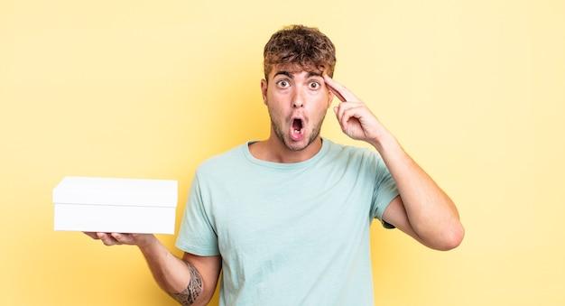Jonge knappe man die verrast kijkt en een nieuwe gedachte, idee of concept realiseert. witte doos concept