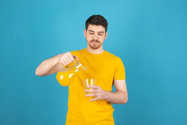 Jonge knappe man die vers sap uit de karaf in het glas giet.