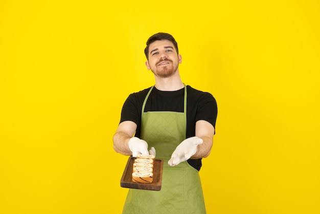 Jonge knappe man die verse cakeplakken toont aan de camera.