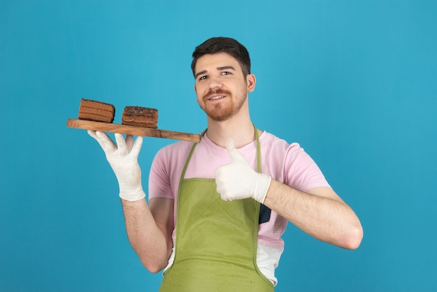 Jonge knappe man die verse cakeplakken vasthoudt en duim omhoog gebaart.