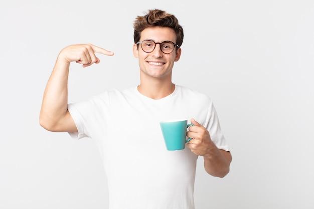 Jonge knappe man die vol vertrouwen glimlacht, wijst naar zijn eigen brede glimlach en een koffiekopje vasthoudt