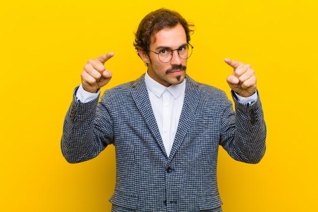Jonge knappe man die vooruit op camera met zowel vingers als boze uitdrukking richt, die u vertelt om uw plicht tegen oranje muur te doen