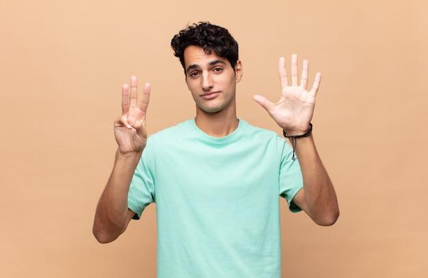 Jonge knappe man die vriendelijk glimlacht en kijkt, nummer acht of achtste met vooruit hand toont, aftellend