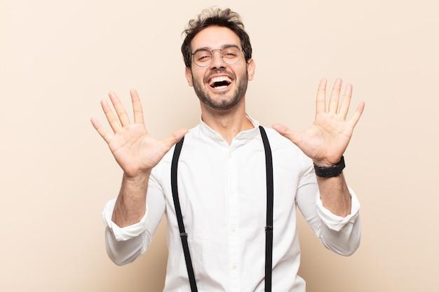 Jonge knappe man die vriendelijk glimlacht en kijkt, nummer tien of tiende met vooruit hand toont, aftellend