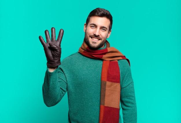 Jonge knappe man die vriendelijk glimlacht en kijkt, nummer vier of vierde met vooruit hand toont, aftellend. koud en winterconcetp