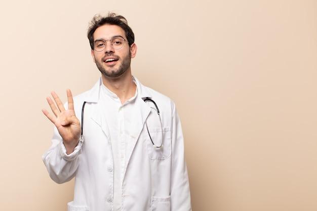 Jonge knappe man die vriendelijk glimlacht en kijkt, nummer vier of vierde met vooruit hand toont, aftellend