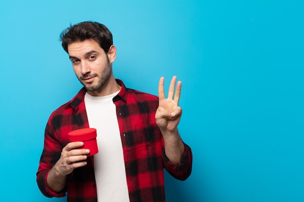 Jonge knappe man die vriendelijk glimlacht kijkt, nummer drie of derde met vooruit hand toont, aftellend