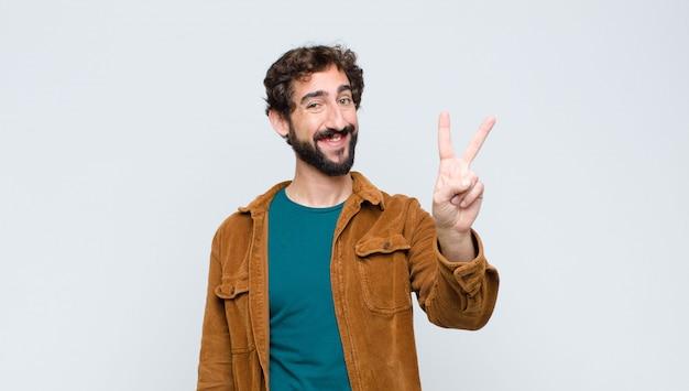 Jonge knappe man die vriendelijk glimlacht kijkt, nummer twee of seconde met vooruit hand toont, aftellend op vlakke muur