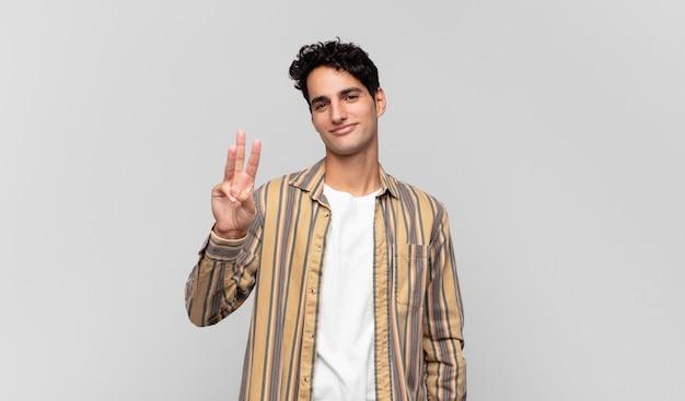 Jonge knappe man die vriendelijk glimlacht kijkt, nummer twee of seconde met vooruit hand toont, aftellend