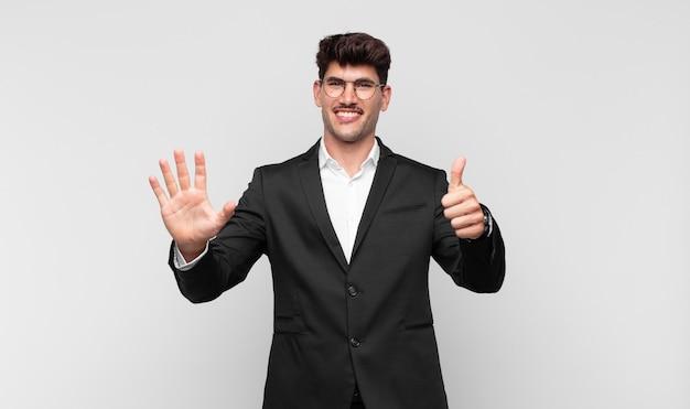 Jonge knappe man die vriendelijk glimlacht kijkt, nummer zes of zesde met vooruit hand toont, aftellend