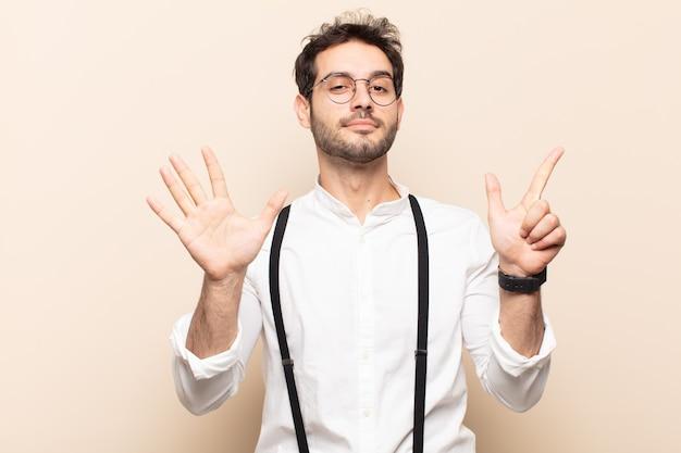 Jonge knappe man die vriendelijk glimlacht kijkt, nummer zeven of zevende met vooruit hand toont, aftellend