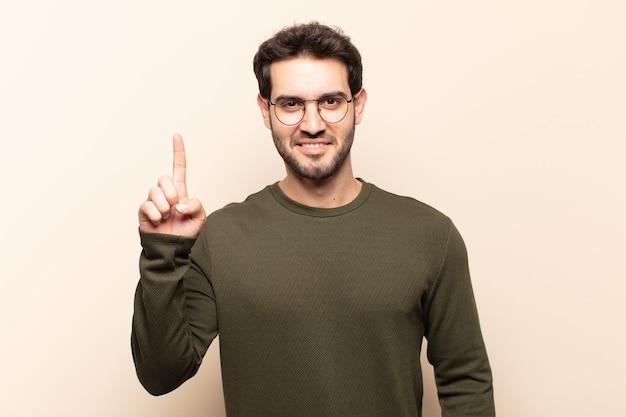 Jonge knappe man die vrolijk en gelukkig glimlacht, naar boven wijzend met één hand om ruimte te kopiëren