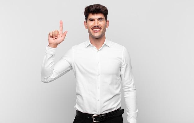 Jonge knappe man die vrolijk en gelukkig lacht en met één hand naar boven wijst om ruimte te kopiëren