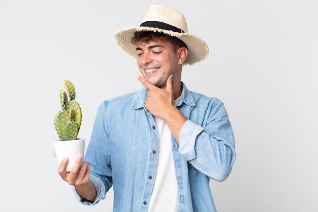 Jonge knappe man die vrolijk lacht en dagdroomt of twijfelt. boer met een decoratieve cactus
