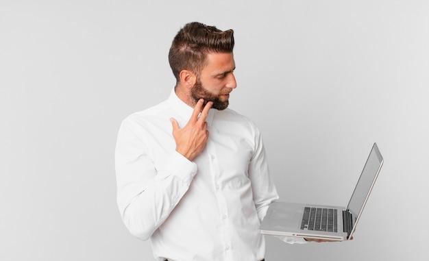 Jonge knappe man die vrolijk lacht en dagdroomt of twijfelt en een laptop vasthoudt