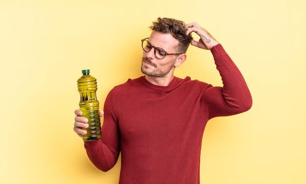Jonge knappe man die vrolijk lacht en dagdroomt of twijfelt. olijfolie concept